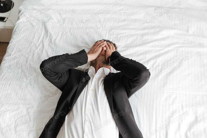 Tired man dressed in suit lying on bed