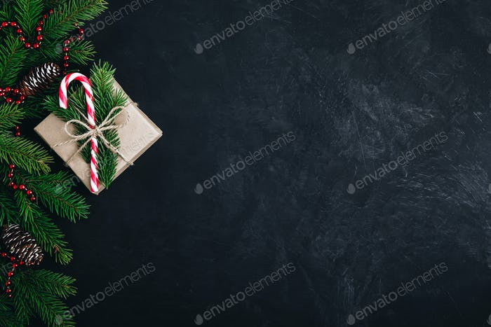 Christmas festive background with christmas tree branches, fir cones and gift box with candy cane.