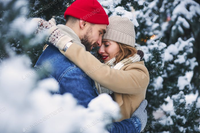 Happy couple in love in winter forest