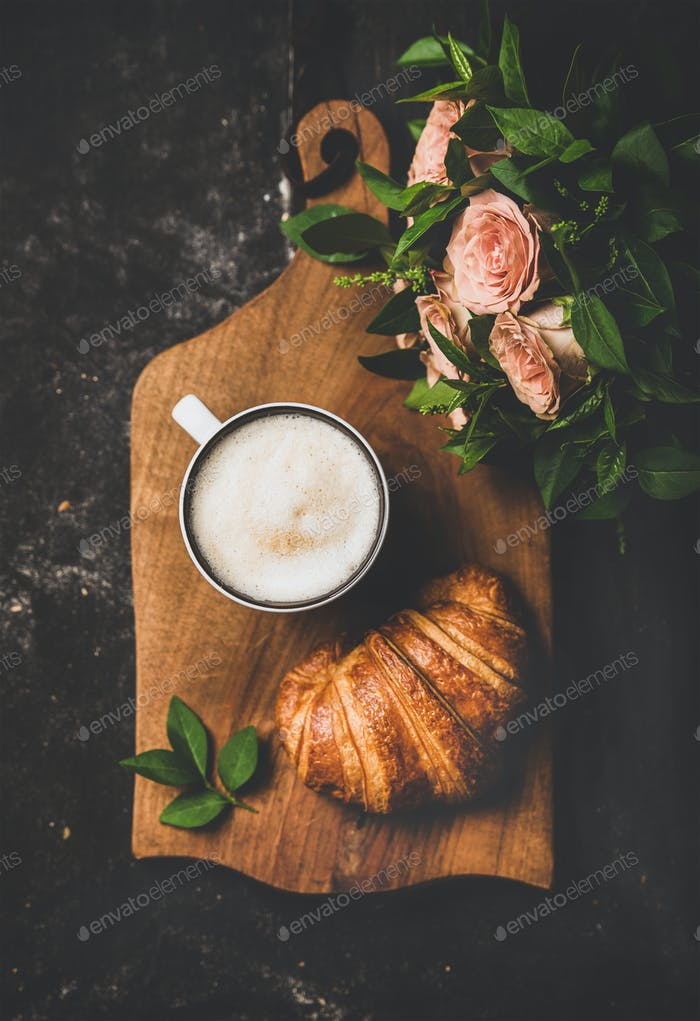 Cup of cappuccino, croissant and bouquet of pink flowers