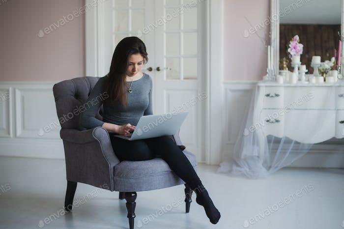 Hübsche Dame arbeitet auf ihrem Laptop während sitzen in einem Sessel