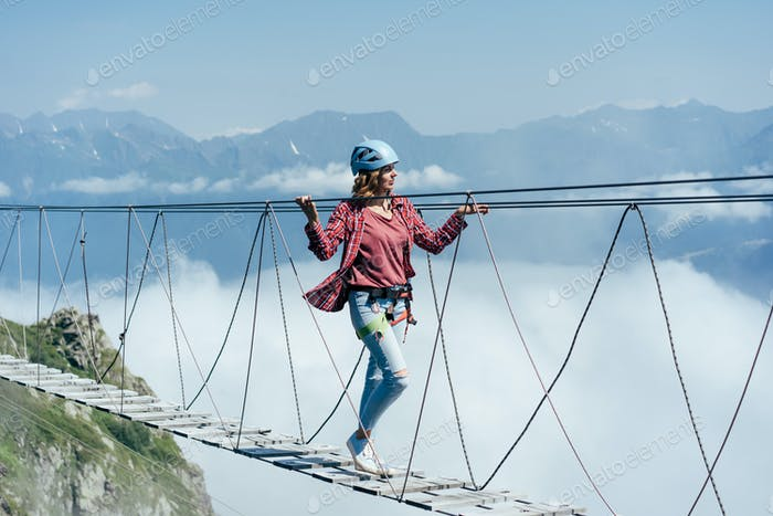 Extreme vacation. A woman walks on a suspension bridge high in the mountains