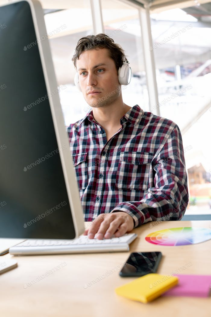 Caucasian male graphic designer listening music on headphone while working on computer at desk