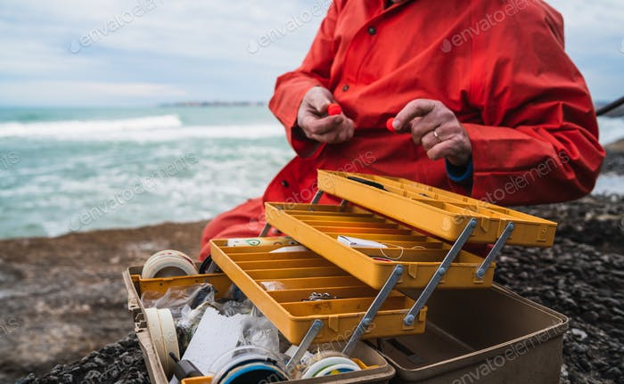 Fisherman with fishing equipment box.