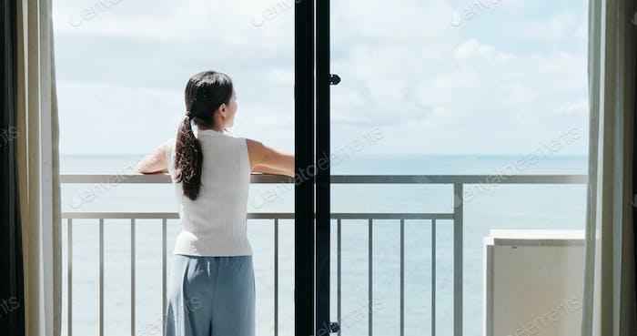 Frau Blick auf das Meer auf dem Balkon