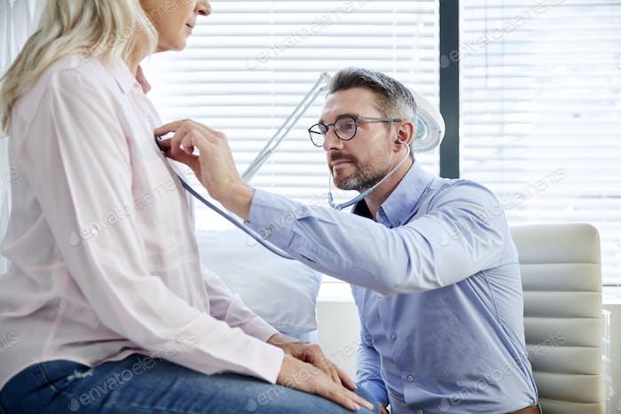 Reifen weiblich Patienten mit medizinische Prüfung mit Arzt in office
