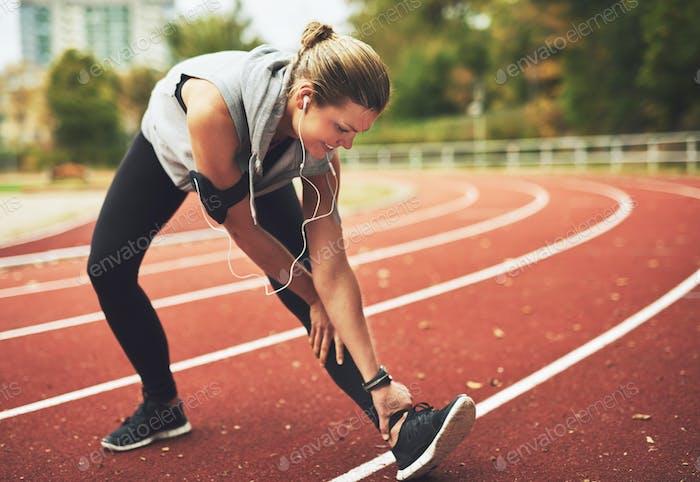 Smiling blonde sportswoman stretching before training