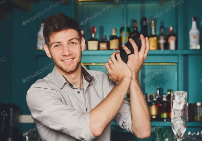 Young handsome barman in bar shaking and mixing alcohol cocktail