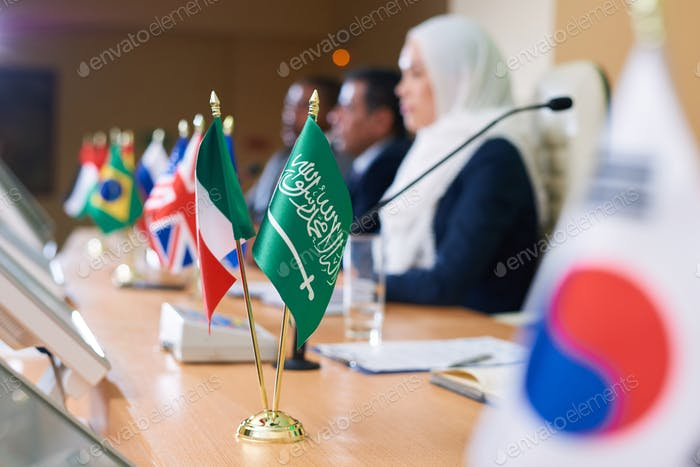 Green flag of muslim country and tricolor one on long table