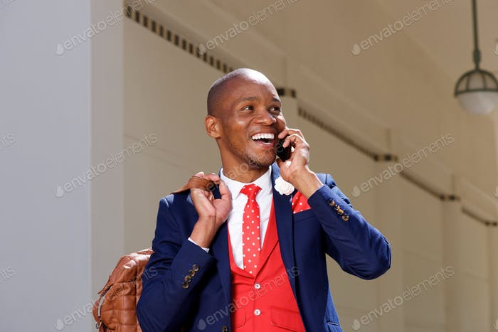 cheerful young african man in suit talking on mobile phone