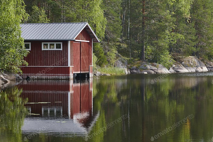 Traditional Finland landscape with lake, forest red wooden house. Horizontal