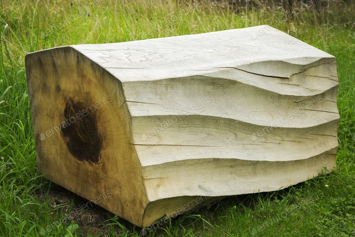 Close up of carved piece of tree trunk with wave pattern lying on grass.