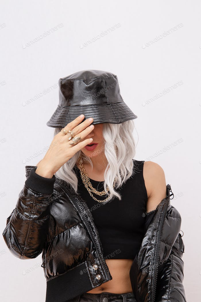 Sexy blonde model in fashion urban street outfit. Trendy black bucket hat and bomber.