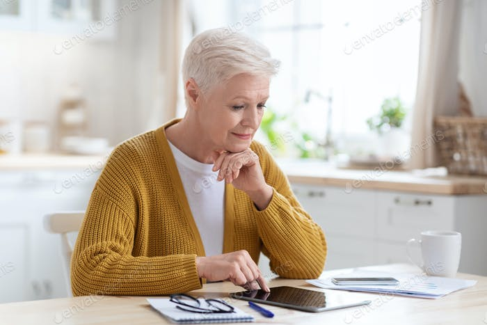 Senior lady business woman sitting in kitchen, using tablet