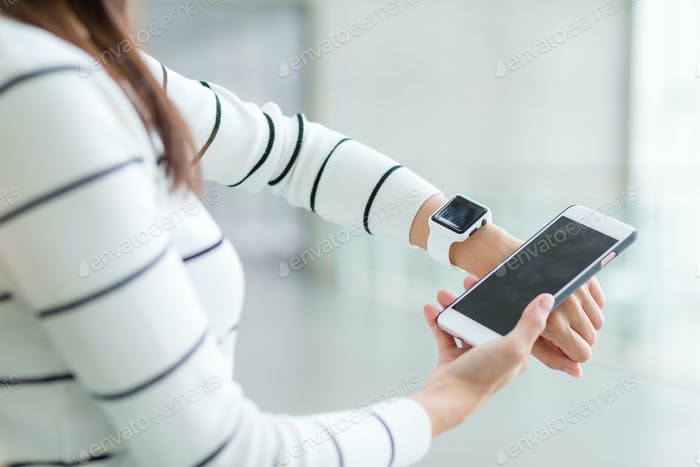 Woman connecting smartwatch and cellphone