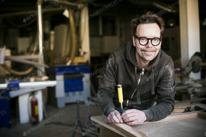 Portrait of smiling carpenter with chisel in workshop