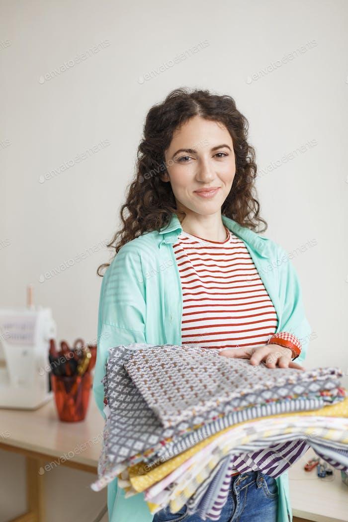 Beautiful smiling seamstress joyfully looking in camera while ho
