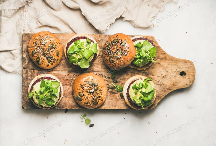 Flat-lay of healthy vegan burgers with beetroot patties on board
