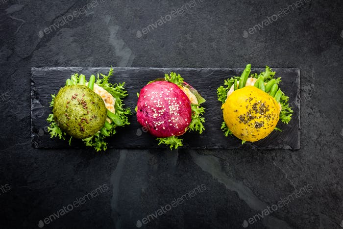 Colored green, yellow and purple burgers on slate board. Top view