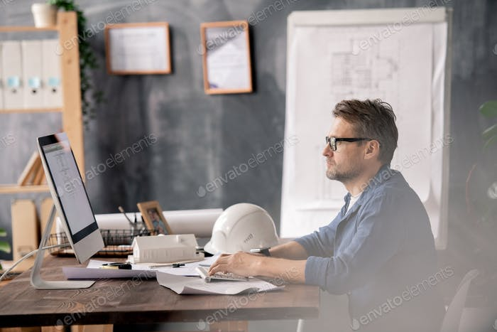 Mature competent engineer in casualwear looking at computer screen and typing