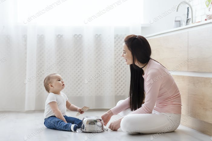 Baby and young mother playing music on kitchen floor