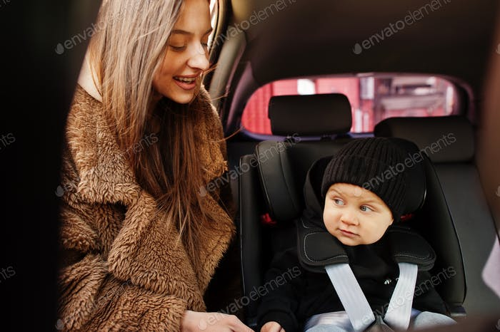 Young mother and child in car. Baby seat on chair. Safety driving concept.