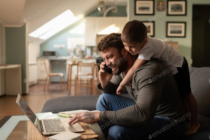 Cheerful father with son working from home