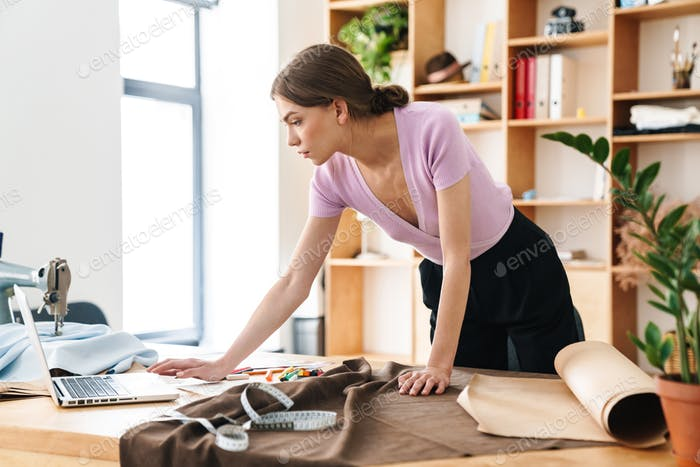 Photo of serious woman fashion designer working with laptop and textile