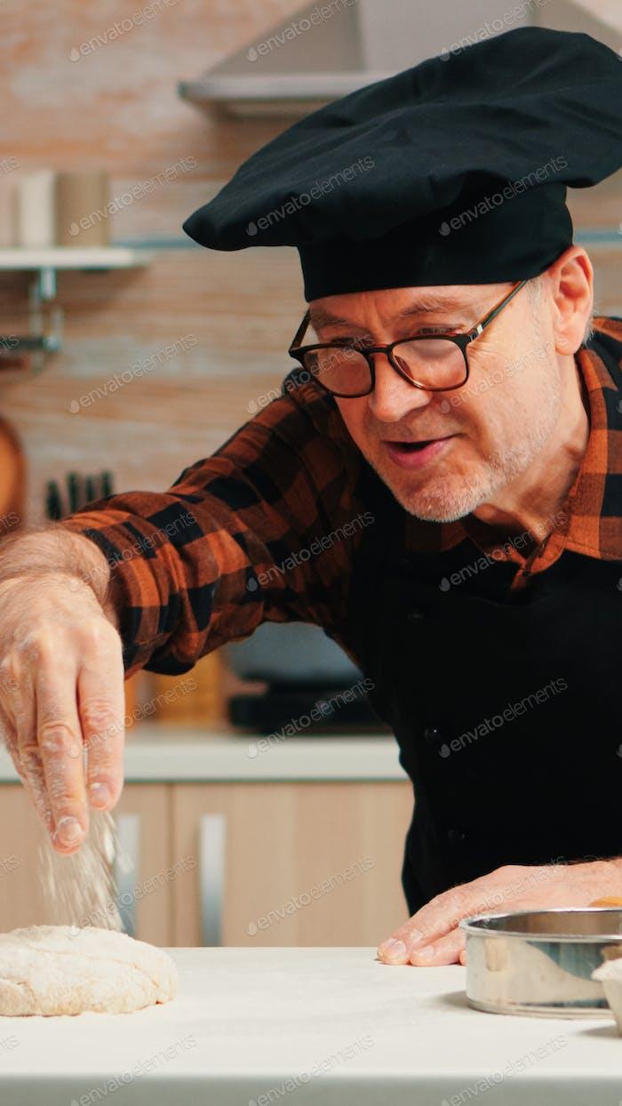 Man sieving flour over dough on table