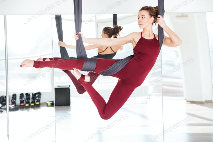 Concentrated beautiful young woman practicing different antigravity yoga positions