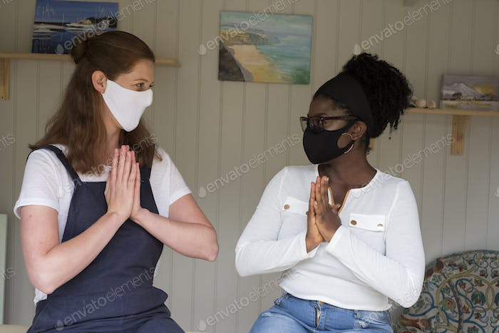Alternative therapy session, practitioner and client, women in face masks with hands together.