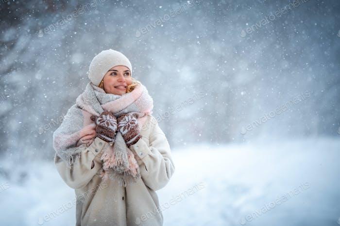 Lächelnde Frau genießt den Winter im Schnee