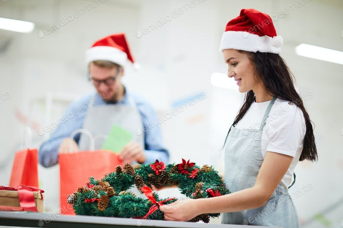 Content florist making holiday wreath