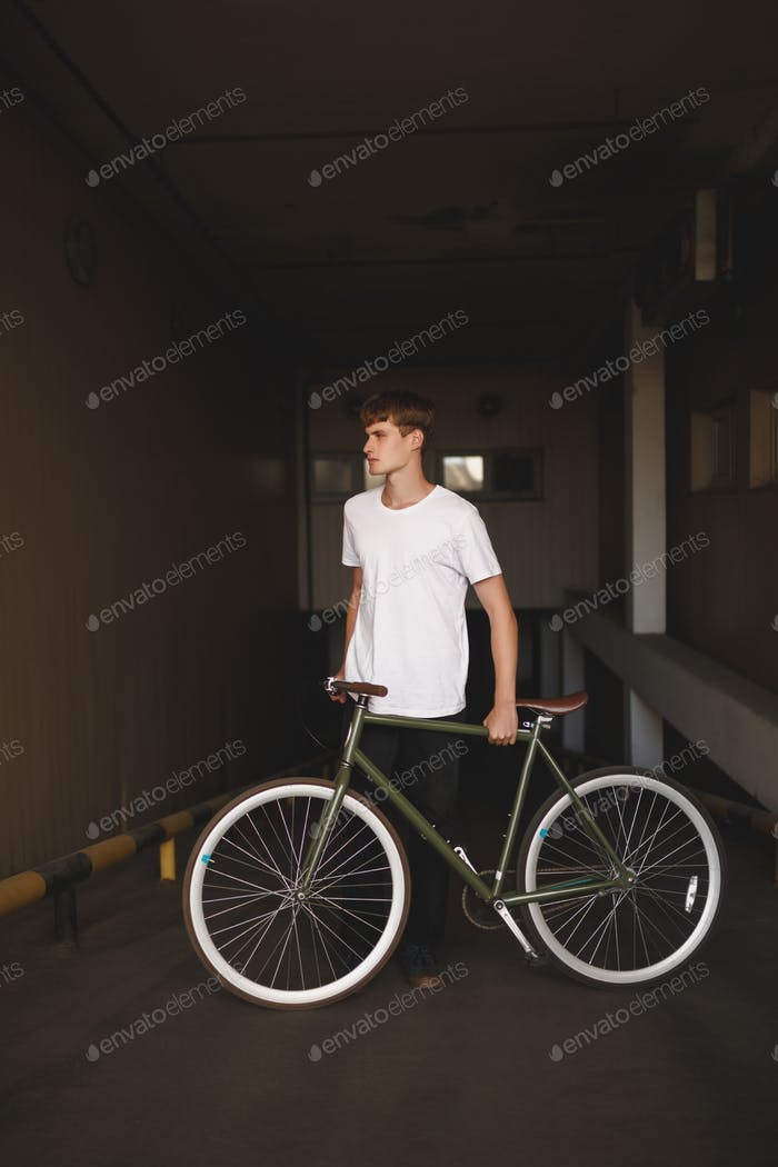 Photo of young thoughtful man in white t-shirt standing with classic bicycle in parking