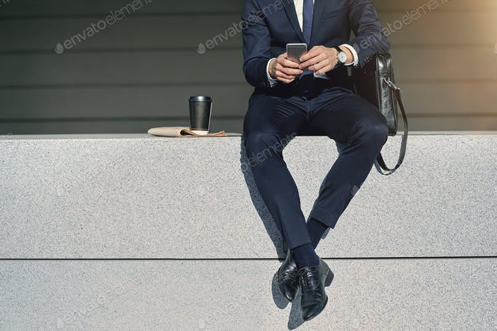 Legs of businessman searching information in smartphone