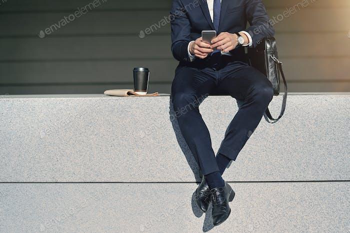 Beine des Geschäftsmanns Suche Informationen im Smartphone
