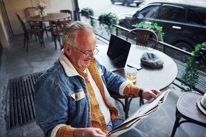 Stilvolle Senior in modischer Kleidung und in Gläsern sitzt im Café und liest Zeitung