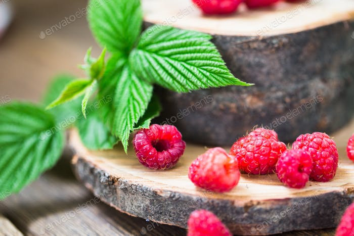 Fresh raspberry with leaves on a wooden table outdoors