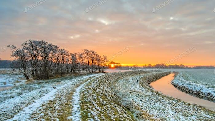 Dike near Meandering River in Frozen grassland landscape