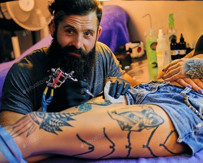 Тату мужчина художник делает татуировку на женскую ногу.