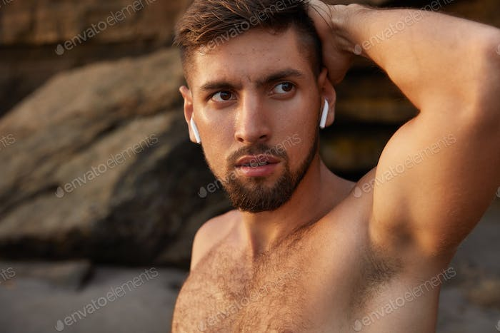Sportsman with serious look, keeps hand behind head, poses half naked against coastline, has thick b