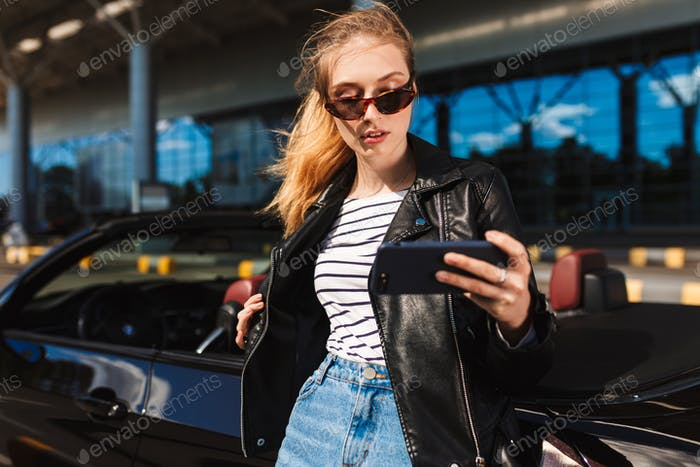 Pretty girl in sunglasses and leather jacket taking photos on ce