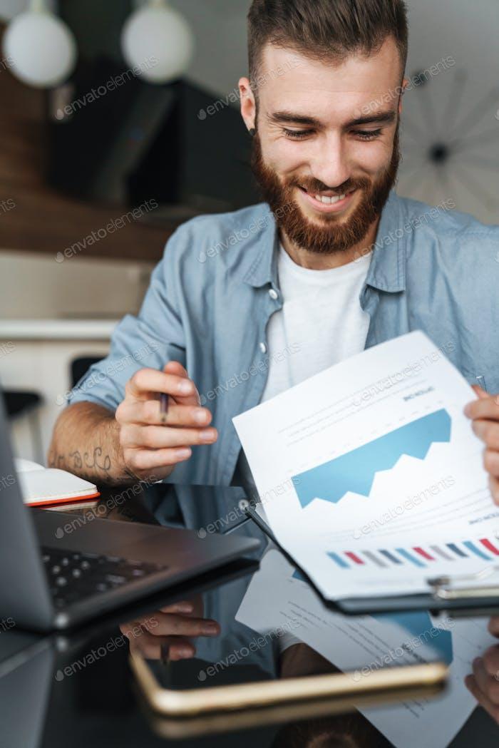 Lächelnd junge bärtige Mann arbeiten auf Laptop-Computer