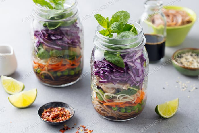 Healthy Asian Salad with Noodles, Vegetables, Chicken and Tofu in Glass Jars. Grey background.