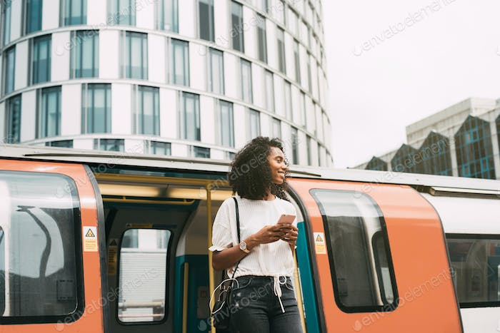 Black woman using mobile phone at london underground