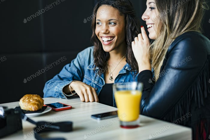 two female mixed race friends having a orange juice and chatting