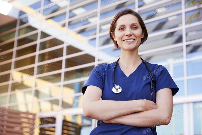 Smiling white female healthcare worker outdoors, waist up