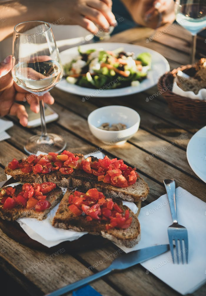Dinner with salad, bruschetta with tomato and white wine