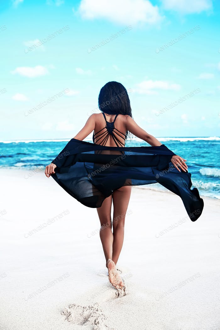 Portrait of beautiful tanned woman posing at the beach