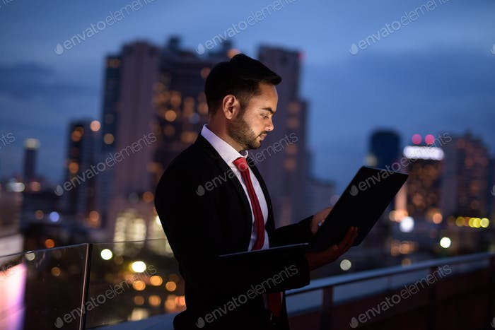 Young bearded Indian businessman against view of the city at nig